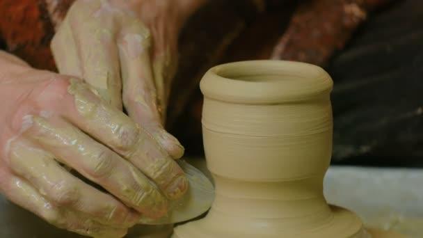 Profesionální potter tvarování hrnek se speciálním nástrojem v keramické dílně
