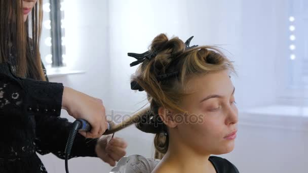 Professional hairdresser doing hairstyle for woman - making curls