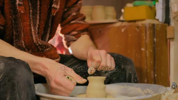 Profesionální potter řezbářské hrnek se speciálním nástrojem v keramické dílně