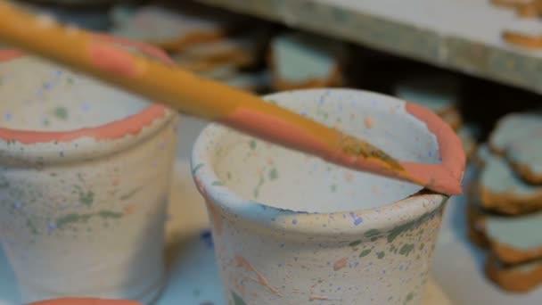 Profesionální mužský potter malba hrnky v keramické dílně