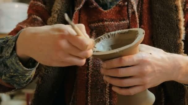 Professionelle Töpfer schnitzen Teil der Vase mit Spezialwerkzeug in Keramikwerkstatt