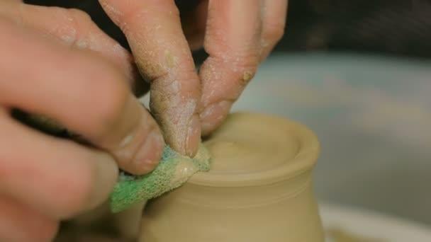 Professionelle Töpfer gestalten Tasse mit Spezialwerkzeug in Keramikwerkstatt