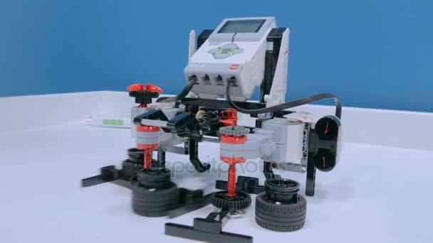 Žena hraje tři hazardní hru s Lego robot na výstavě