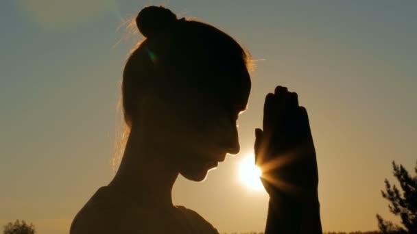 Sportovní žena se modlí v lese při západu slunce