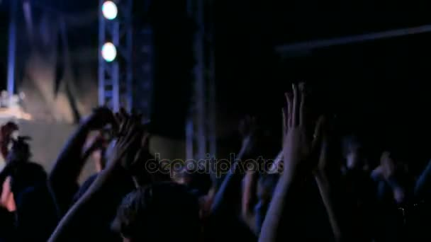 Silhouettes of people partying and clapping at rock concert in front of stage