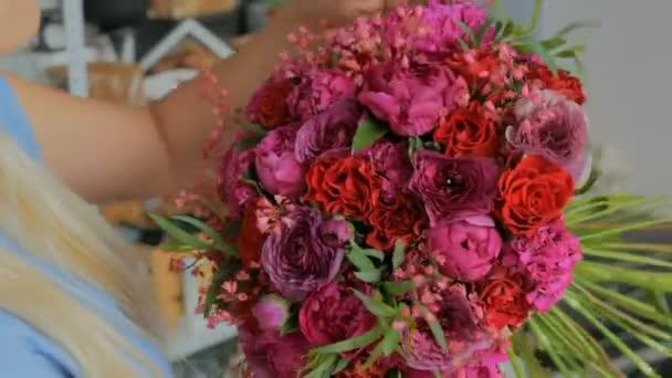 Florista držení a kontrola kytice ve studiu