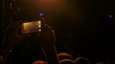 Unrecognizable hands silhouette recording video of music concert with smartphone