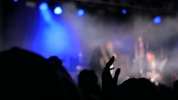 Sziluettek ember bulizás és taps a rock koncert, színpad előtt