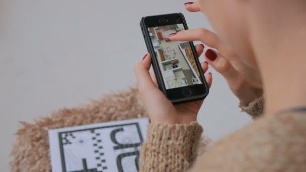 Žena smartphone pomocí rozšířené reality aplikace, kontrola plán virtuální dům