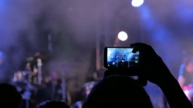 Hand silhouette recording video of live music concert with smartphone