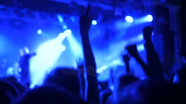 Sziluettek ember bulizás rock koncerten a színpad előtt.