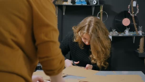 Due decoratori professionali delle donne, progettisti che lavorano con carta kraft