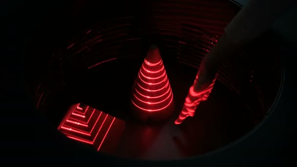 Optical illusion with red lasers, woman hand and geometric objects
