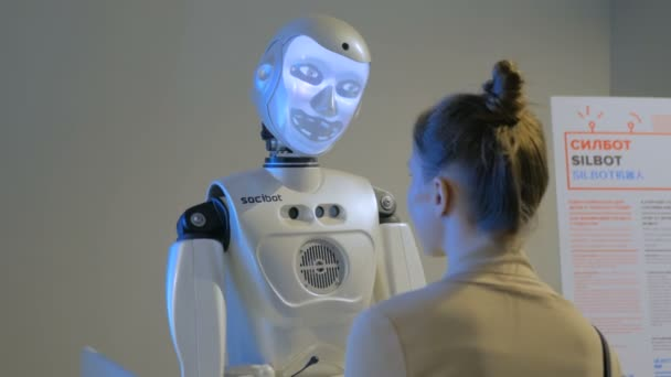 Funny humanoid robot with display face talking with woman, technology exhibition