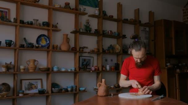 3 Schüsse. Professionelle Gestaltung von trockenem Ton Cup mit Spezialwerkzeug in Keramikwerkstatt potter