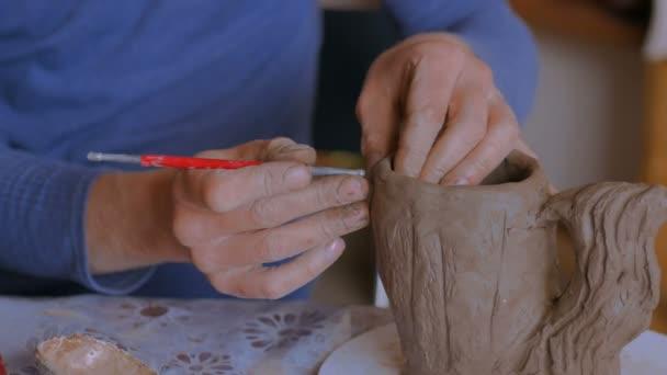 3 Schüsse. Professionelle Töpfer machen Muster auf Ton-Becher mit Spezialwerkzeug in Keramikwerkstatt