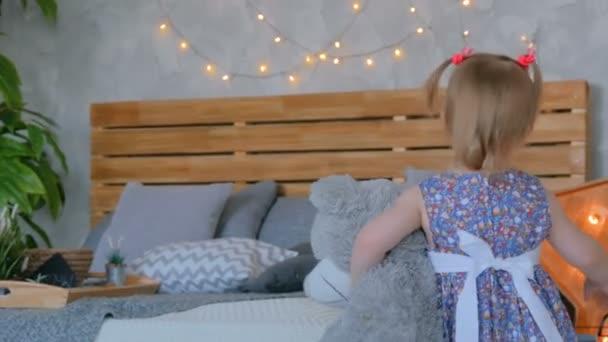 Portrét legrační malá holčička s panenkou medvěd doma