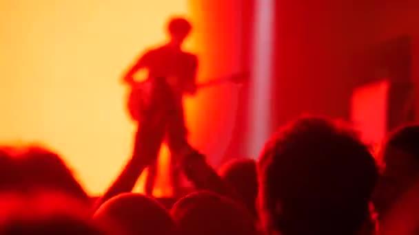 Siluety lidí pařících a tleskajících na rockovém koncertě s červeným světlem
