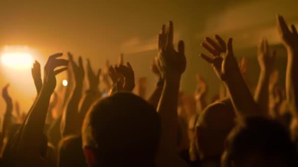Super zpomalený film: siluety lidí pařících a tleskajících na rockovém koncertě