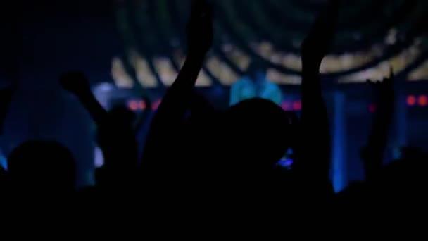 Zpomalený pohyb: mužská silueta párty a tleskání na rockovém koncertě