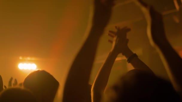 Szuper lassított felvétel: a rock koncerten bulizó és tapsoló emberek sziluettjei