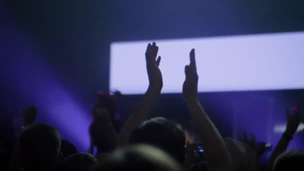 Super zpomalený film: mužská silueta párty a tleskání na rockovém koncertě