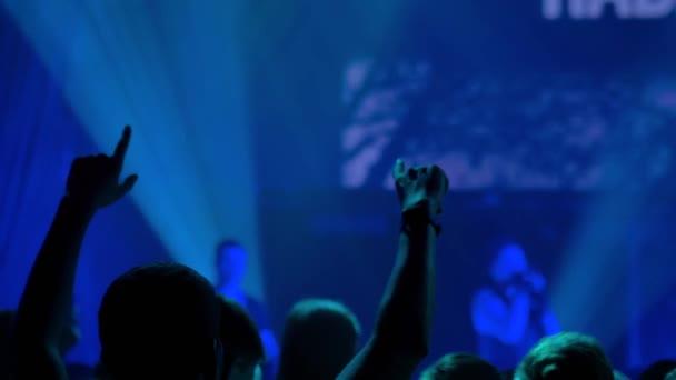 Zpomalený pohyb: siluety muže mávajícího rukama na rockovém koncertě před jevištěm