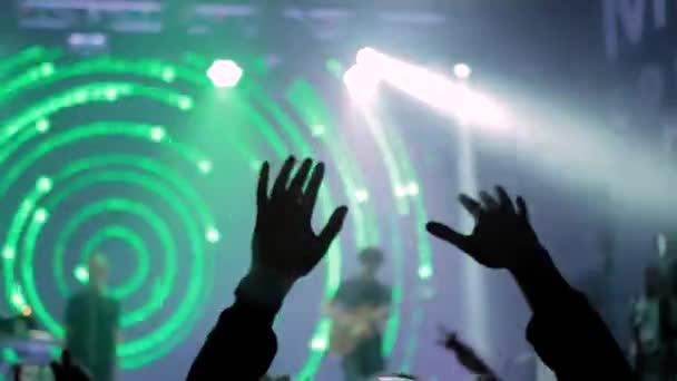 Muž silueta párty na rockovém koncertě před jevištěm se zeleným světlem