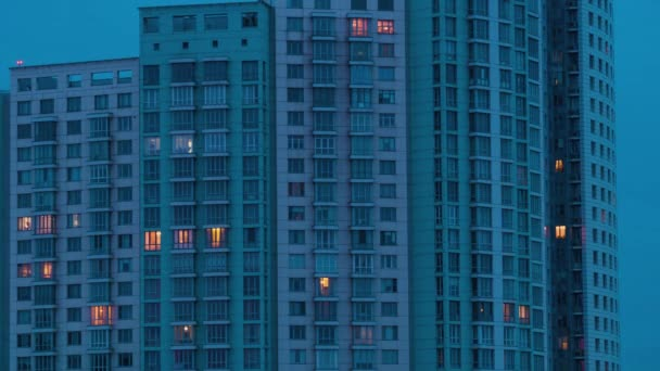 Timelapse of living apartment building windows at dusk to night - facade view