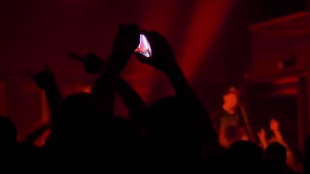 Zpomalený pohyb: lidé nahrávají video z koncertu živé hudby s chytrým telefonem