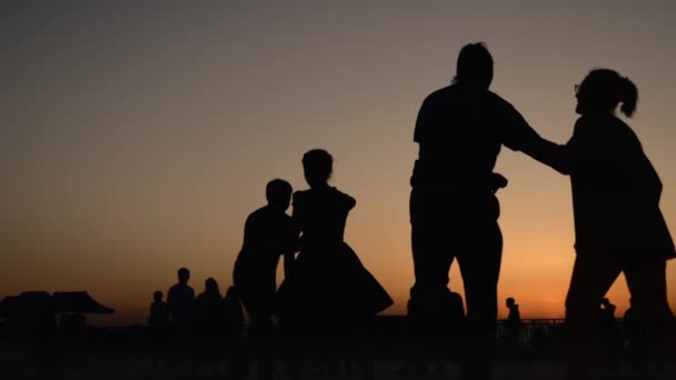 Romantic couples silhouette dancing against sky at sunset - super slow motion