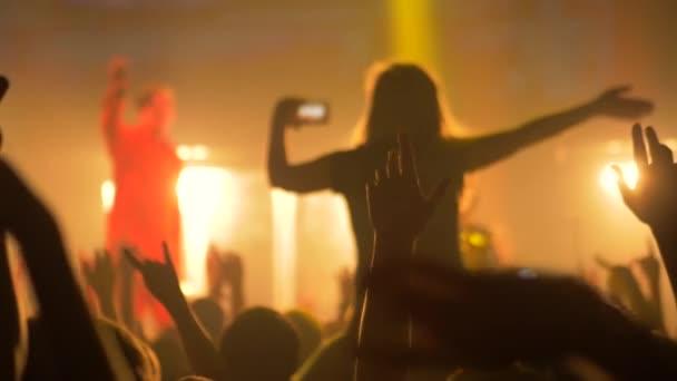 Super zpomalený film: lidé mávají rukama na rockovém koncertě před jevištěm