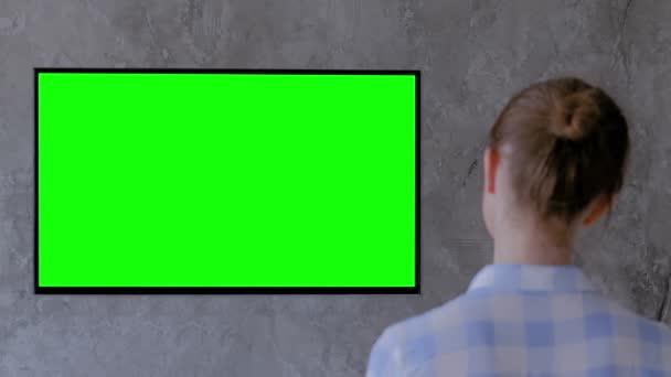 Zöld képernyő koncepció - nő néz lapos intelligens led TV zöld kijelzővel