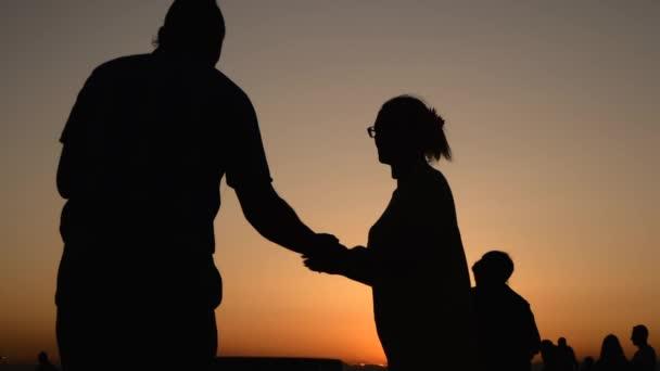Menschen Silhouetten lernen, wie man am Kai bei Sonnenuntergang tanzen - Super Zeitlupe