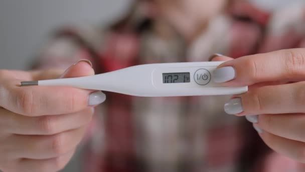 Close up: woman showing digital medical thermometer with high temperature