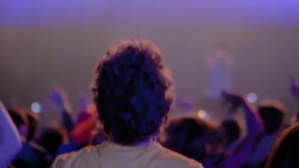Zpomalený film: kudrnatý teenager paří na rockovém koncertě před pódiem