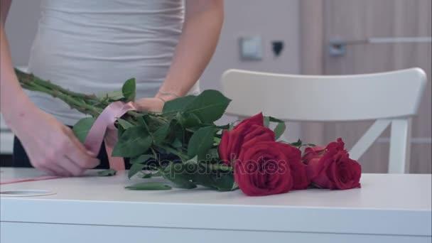 Mladá žena vázací stuhou luk na červené růže kytice