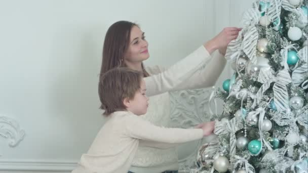 Matka a její syn, zdobení vánočního stromu v obývacím pokoji