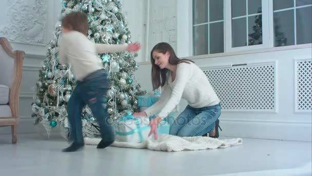 Malý chlapec pomáhal jeho matka může dárkové krabice pod vánoční stromeček