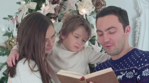 Mladý otec čtení Vánoční příběh, zatímco matka a jejich šťastný syn tajně šeptat