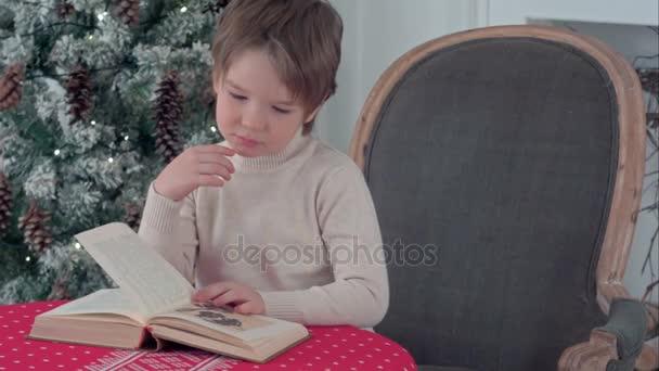 Vážné malý chlapec s knihou na Štědrý den