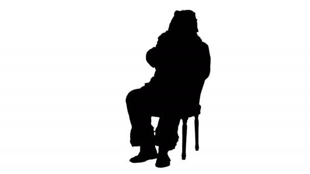 Silueta Santa Claus sedí na židli s písmeny v rukou