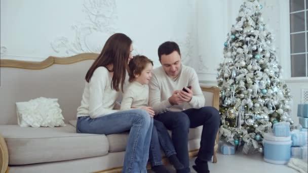 Mladá šťastná rodina sleduje jejich fotografie na telefonu a směje se