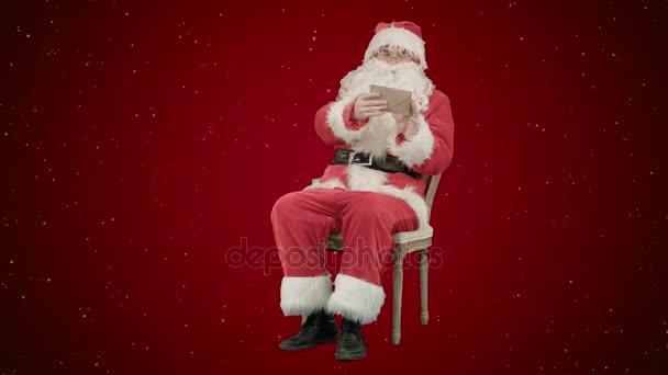 Santa Claus sedí na židli s písmeny v rukou na červeném pozadí se sněhem