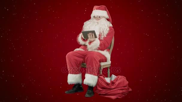 Santa Claus mit Tablet-PC, Internet surfen und kommunizieren in sozialen Medien mit Kindern auf rotem Grund mit Schnee