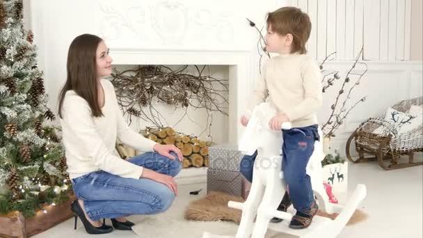 Malý chlapec na koni dřevěné houpací koně a mluví s jeho matkou, sedí u vánočního stromu