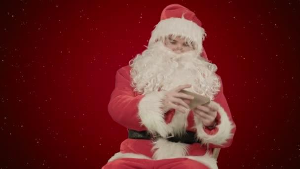 Santa vánoční dopis nebo seznamu přání na červeném pozadí se sněhem
