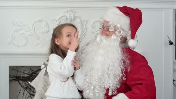 Santa Claus sedí v křesle s holčička sní o její vánoční dárky
