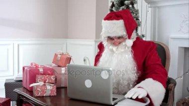 Představuje moderní Santa Claus pracoval na jeho laptopu a příprava