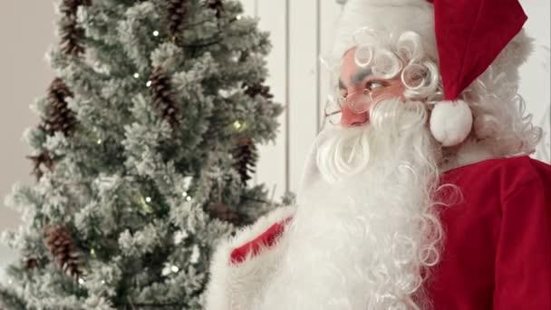 Veselý Santa Claus posezení u vánočního stromu a mluví o telefonu